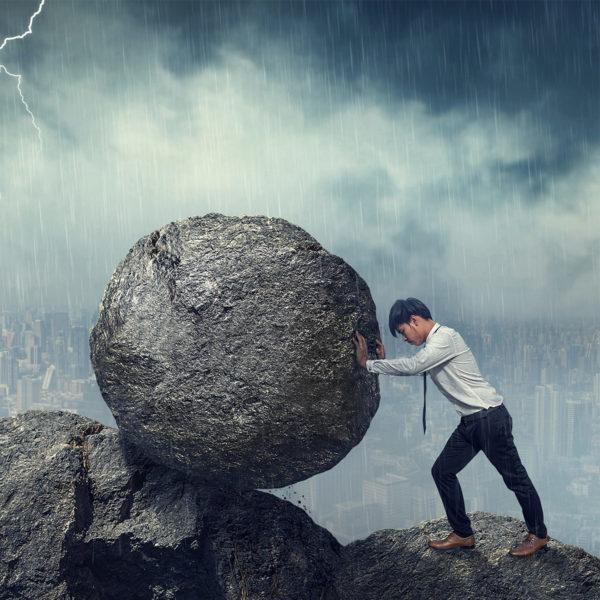 Mann rollt einen Felsbrocken auf einen Berg